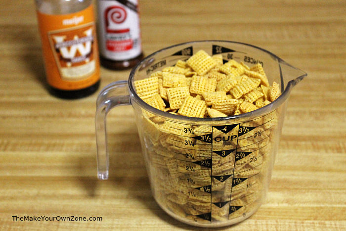 A measuring cup of chex cereal to make homemade snack mix