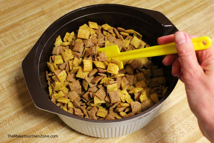 Stirring homemade chex mix in a bowl