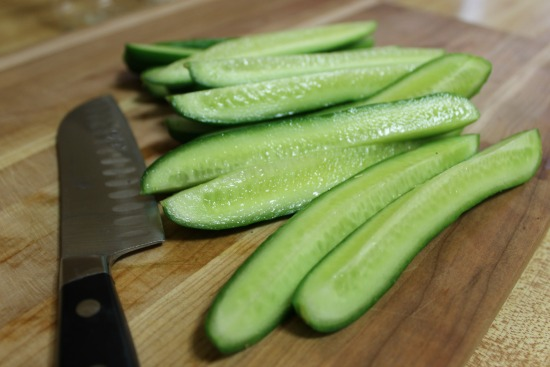 cutting up cucumbers t make homemade pickles