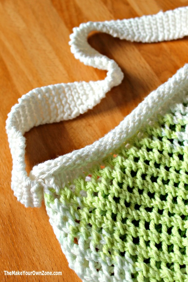 A knit string bag with a rolled brim and a garter stitch handle