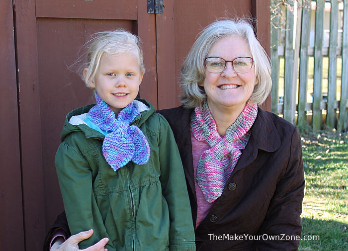 Homemade knit scarf on an adult and a child