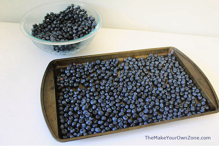 Freezing blueberries by putting them on a sheet pan first