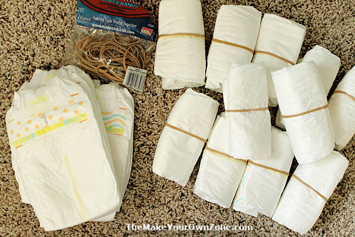 Rolling up diapers to make a diaper cake for a baby shower